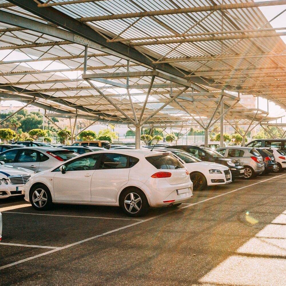 Cars on a covered parking lot in sunny summer day