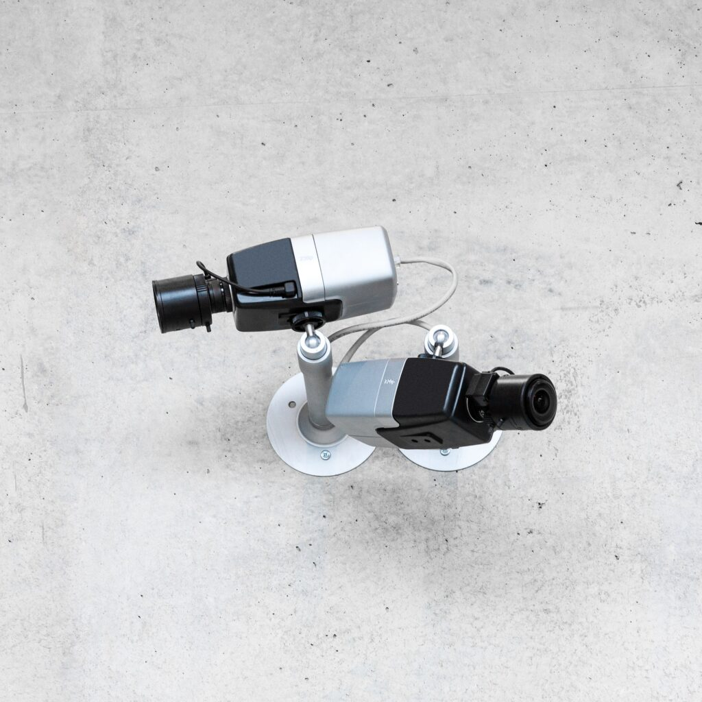 Two modern cctv security cameras on concrete wall