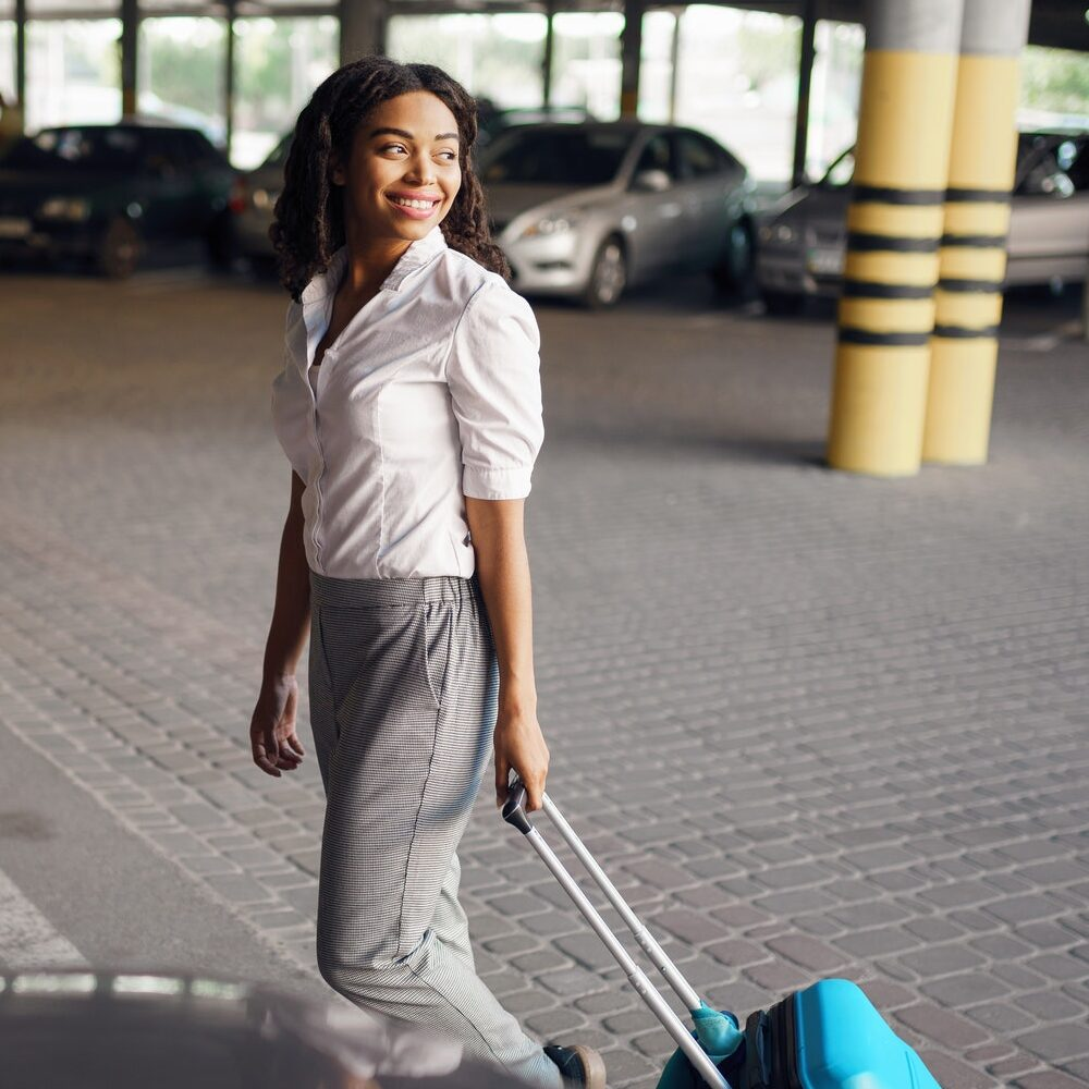 Young woman with suitcase in car parking